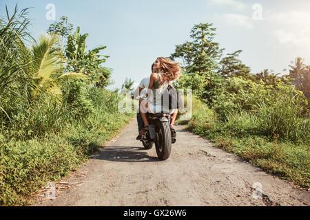 Vista traseira do jovem casal cavalo motociclo do caminho rural. Mulher com o namorado a cavalo na moto em um dia Foto de Stock
