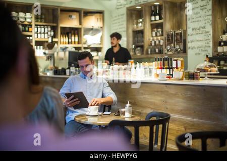 Homem sentado no café browsing tablet digital Foto de Stock