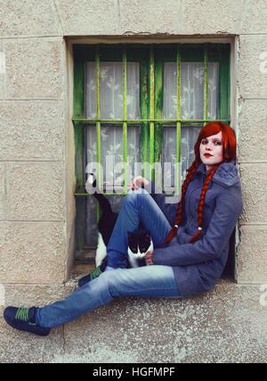 Jovem mulher ruiva, com dois longos braids, sentado perto de uma janela antiga Foto de Stock
