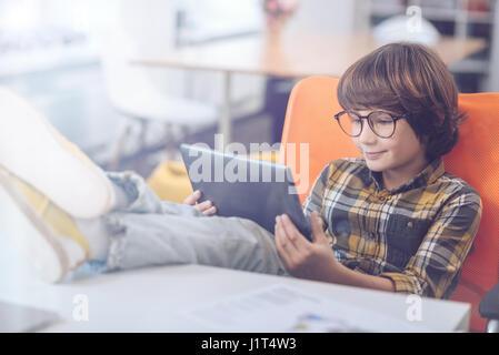 Boy usando digital tablet com pés para cima Foto de Stock