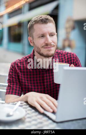 Jovem no café ao ar livre trabalhando no laptop Foto de Stock