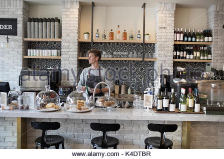 Café masculino de trabalho proprietário reflexivos atrás do balcão, olhando de distância Foto de Stock