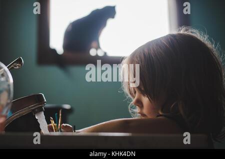 Um toddler girl pintura de lavar suas mãos em um banheiro pia. Foto de Stock