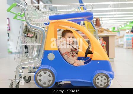 Cute bebê menino sentado no carrinho de compras em um supermercado ou loja de alimentos Foto de Stock