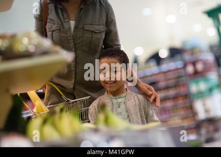 Menino olhando para as bananas na mercearia Foto de Stock