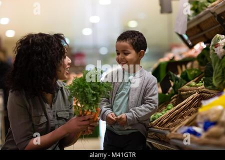 Boy escolher cenouras na mercearia Foto de Stock