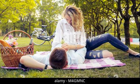 Picnik lindo casal no parque em um dia ensolarado de verão. Foto de Stock
