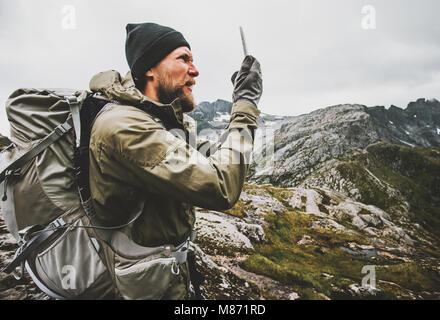 Homem usando o navegador GPS do smartphone viajante verificar coordenadas caminhadas nas montanhas com o conceito Foto de Stock