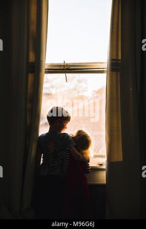Crianças abraçando junto ao espaço da janela dim Foto de Stock