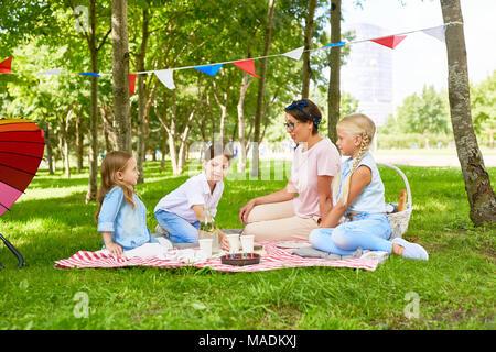 Três meninas e jovem mulher com um piquenique no parque público no gramado verde, não muito longe do parque infantil Foto de Stock