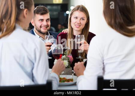 Os amigos estão a jantar no restaurante interior. Foto de Stock