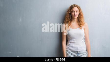 Jovem mulher ruiva grunge cinza sobre a parede com uma expressão confiante no rosto inteligente pensar sério Foto de Stock