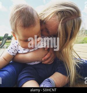 Rapariga a beijar e abraçar seu bebê irmão Foto de Stock