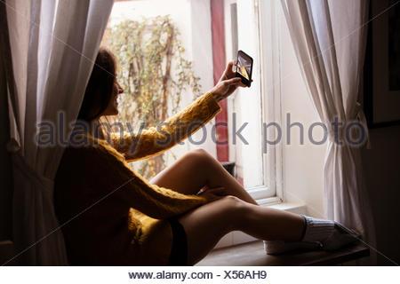 Jovem mulher tendo um selfie perto da janela Foto de Stock